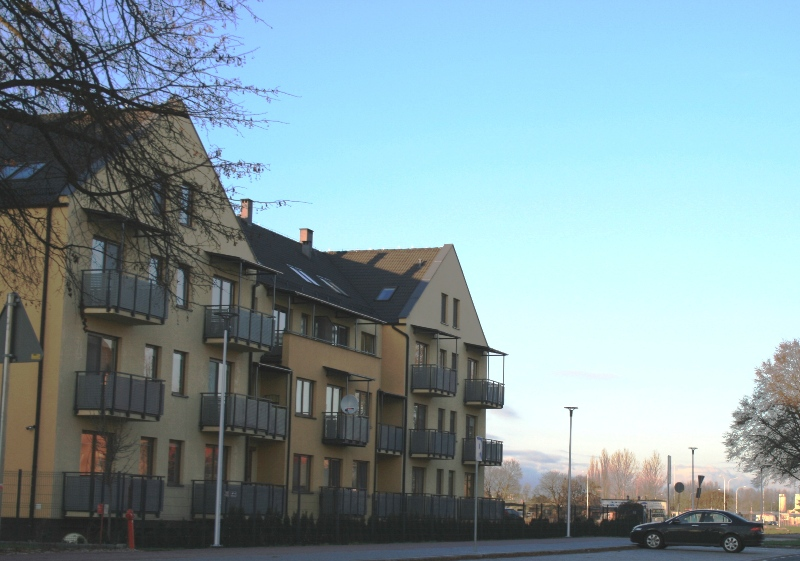 """zdjęcie powyżej - widok na pustą działkę (za tzw. """"żółtym"""" budynkiem Abity) przeznaczoną pod zabudowę budynkiem wielorodzinnym poniżej - grafika obowiązującego mpzp z zazanczoną na czerwono działką (Mw4) i linią zabudowy nowego budynku"""
