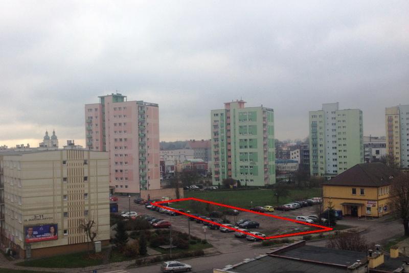 zdjęcie powyżej - widok na pustą działkę (zaznaczona kolorem) przeznaczoną pod zabudowę budynkiem wielorodzinnym TBSu